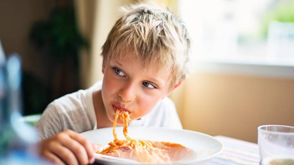 Ein Junge isst Spaghetti und grinst