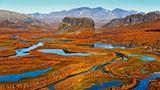 Herbst in Schwedisch-Lappland: Das Flussdelta des Rapaälven mit seinen weit verzweigten Flussläufen erstrahlt in bunten Farben, im Bildzentrum der markante Felsklotz Nammatj. Die Berge im Hintergrund gehören bereits zum Nationalpark Sarek.