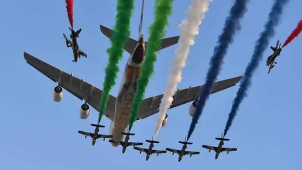 Mehrere Trainingsflugzeuge des Kunstflugdemonstrationsteams der United Arab Emirates Air Force verfolgen einen Airbus A380 von Etihad Airways.