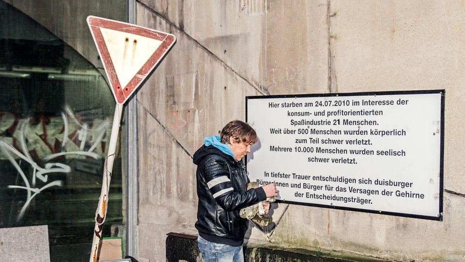 Teich vor einer Gedenktafel, die wütende Bürger bald nach dem Unglück aufgehängt haben