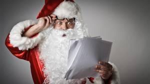 Ein Weihnachtsmann guckt verwundert auf einen Wunschzettel