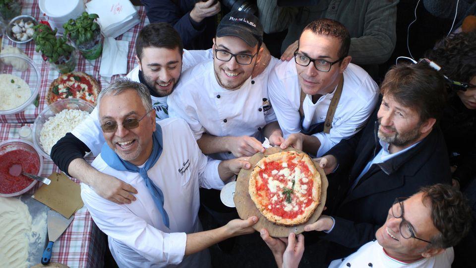 Stolz präsentieren neapolitanische Pizzaioli (italienisch für Pizzabäcker) eine Pizza Margherita, die ab sofort zum Kulturerbe der Menschheit gehört.