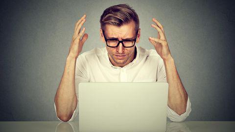Ein Mann schaut verärgert auf seinen Laptop