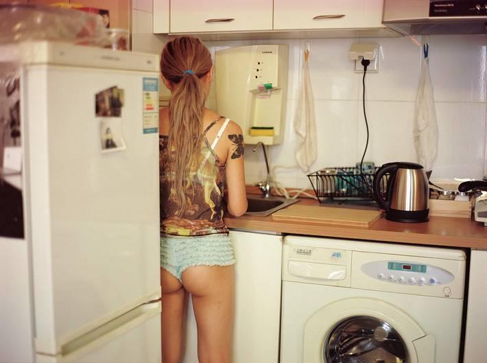 Eine leicht bekleidete Dame steht mit dem Rücken zur Kamera in der Küche