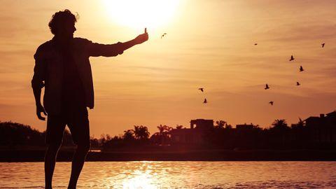 Ein junger Mann steht im Sonnenuntergang am Wasser
