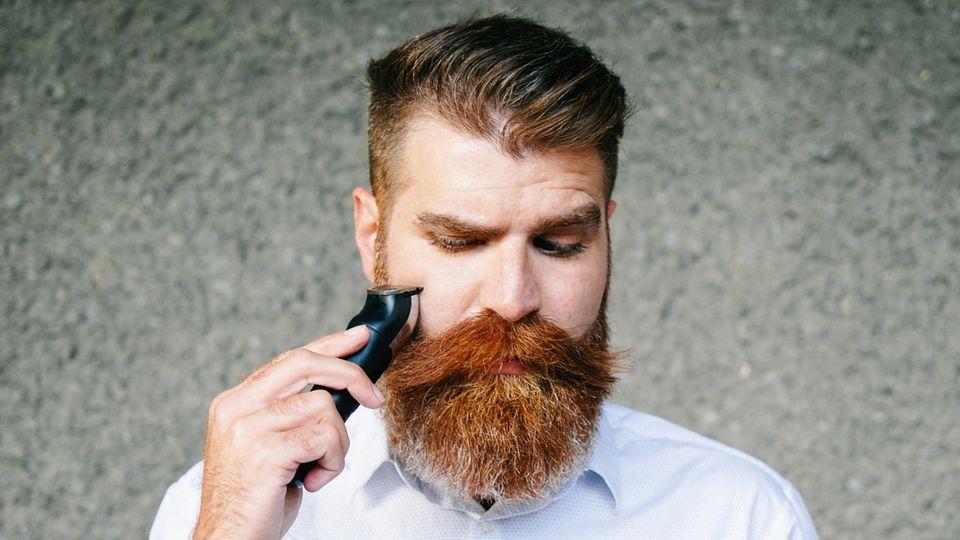 Mann trimmt sich rotfarbenden Vollbart