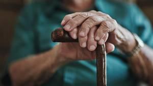 Ein älterer Herr hält einen Gehstock