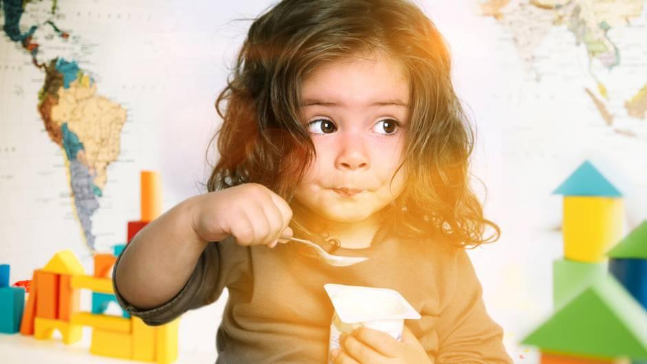 Ein Mädchen löffelt einen Joghurt