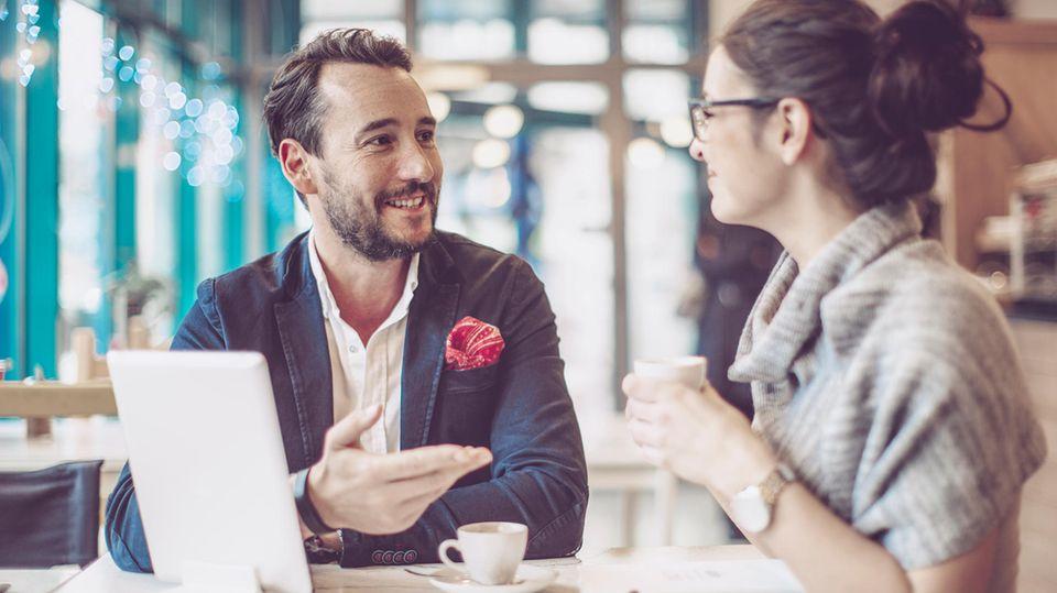 Ein Mann und eine Frau schütteln in einem Bewerbungsgespräch Hände