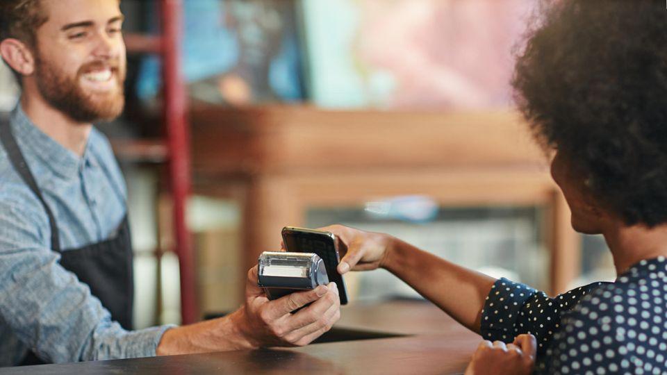 Eine Frau zahlt in einem Laden mit dem Smartphone