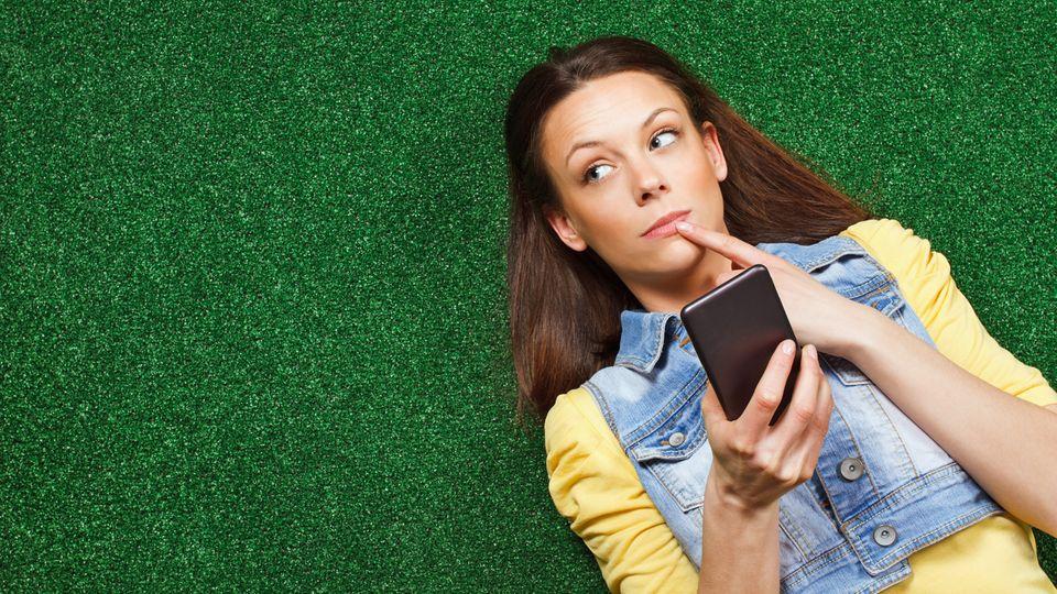Eine junge Frau liegt auf einer Wiese und denkt mit dem Smartphone in der Hand nach