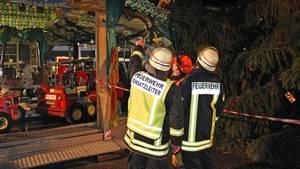 Nachrichten aus Deutschland: Zwei Feuerwehrmänner stehen vor dem zerstörten Kinderkarussell in Eschweiler bei Aachen