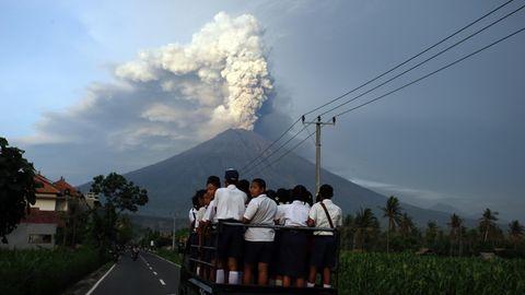 Ein Kleintransporter auf Bali fährt mit Schülern auf der Ladefläche auf den Vulkan Gunung Agung zu, der Rauch und Asche speiht
