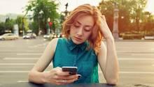 Eine Frau schaut frustriert auf ihr iPhone