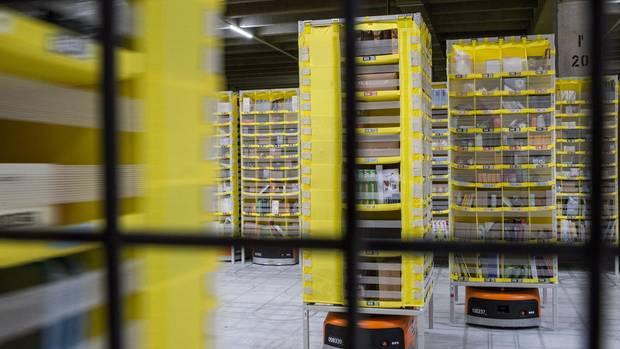 In den neuen Logistikzentren stehen Regale eng an eng, orangefarbene Roboter tragen sie