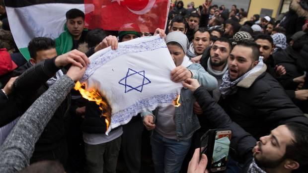 Pro-palästinensische Demonstranten verbrennen eine Israel-Flagge in Berlin