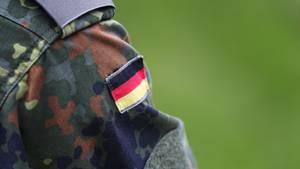 Die Schulter eines Bundeswehrsoldaten in Tarnfleck-Uniform und mit Deutschland-Flagge