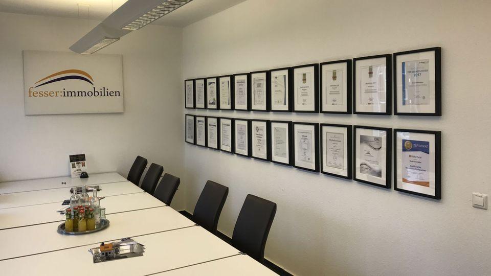 "Besprechungsraum bei ""fesser immobilien"": An der Wand hängen Zertifikate und Auszeichnungen"