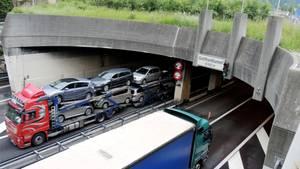 An einem Ende des Gotthard-Tunnels fahren Lastwagen auf der Autobahn in den Tunnel hinein und heraus
