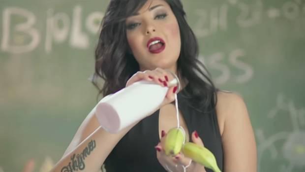 Die schwarzhaarige Sängerin Shyma steht vor einer Schultafel und gießt aus einer Flasche Milch über Bananen in ihrer linken Hand