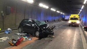 Ein schwarzer Kleinwagen steht quer im Gotthard-Tunnel. Die Front ist komplett zerstört. Im Hintergrund steht ein Krankenwagen.