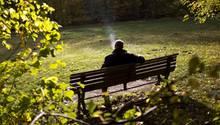 Mann raucht auf Parkbank