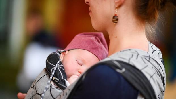 Eine junge Mutter trägt ihr Baby auf der Brust