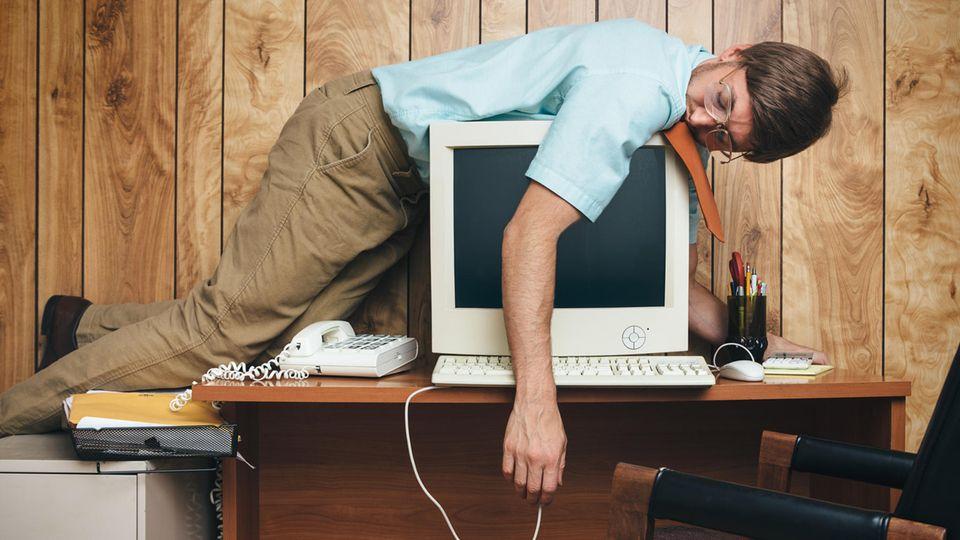 Mann liegt müde auf einem Computer