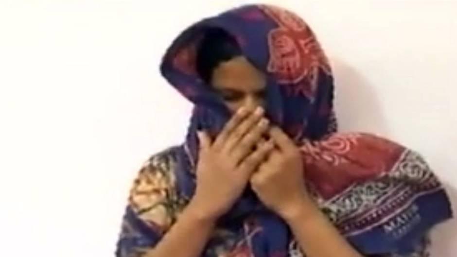 Eine Frau in traditioneller indischer Kleidung zieht sich ihr Kopftuch ins Gesicht und verbirgt Mund und Nase mit ihren Händen