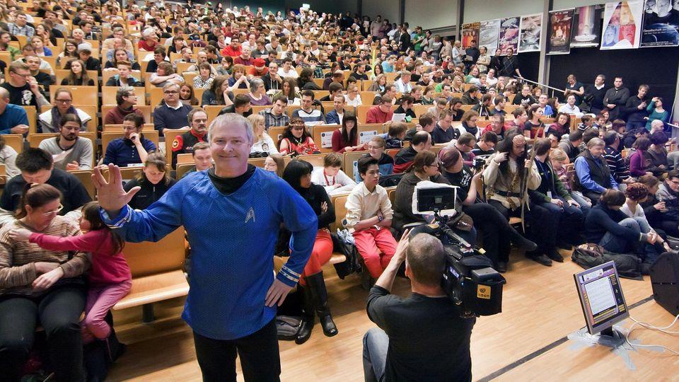 Voll besetzter Hörsaal bei der Star Trek Vorlesung - Hubert Zitt im blauen Starfleet-Shirt zeigt den Vulkanier-Gruß
