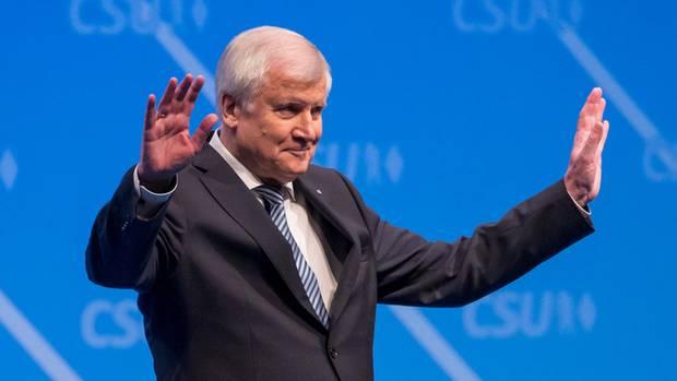 Horst Seehofer hält grüßend beide Arme hoch - Er ist beim CSU-Parteitag als Parteichef bestätigt worden