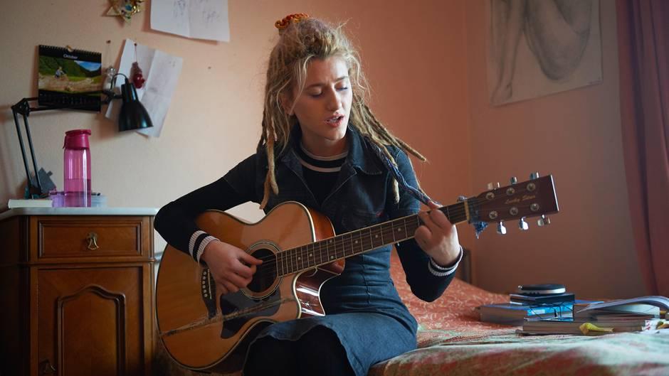 Natia Todua auf sitzt mit einer Gitarre auf dem Bett.