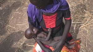 Eine Frau hält am Standort einer Essensausgabe in Malualkuel im Sudan ihre abgemagerte Tochter im Arm