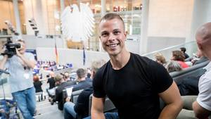 Ein muskulöser blonder Mann sitzt lächelnd in Jeans und T-Shirt auf der Zuschauertribüne im Bundestag
