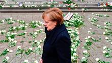 Im dunklen Mantel geht Angela Merkel über den Breitscheidplatz, auf dem weiße Rosen für die Opfer des Terroranschlag liegen