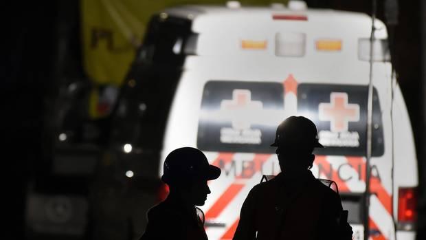 Vor einem mexikanischen Rettungswagen zeichnen sich die Silhouetten zweier Männer mit Helmen ab
