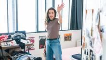 Ein jugendliches Mädchen steht mit vorwurfsvoller Miene in ihrem Zimmer
