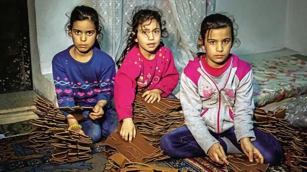 Syrische Mädchen stecken für Damensandalen Nieten in Laschen