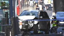 Ein Polizist fotografiert das Fahrzeug, mit dem ein Mann in Melbourne eine Menschenmenge gerast ist
