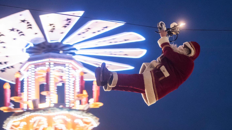 Der Hochseilartist Falko Traber seilt sich über dem Weihnachtsmarkt als Weihnachtsmann verkleidet von einem Dach ab