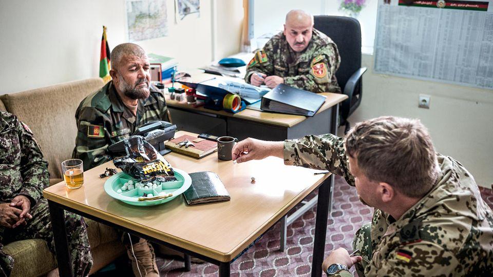Zuckerkügelchen gegen Schokopralinen: Kerstens erklärt Oberstleutnant Abdul Latif (M.) ein militärisches Manöver