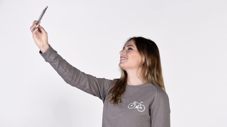 Eine junge Frau in grauem Sweatshirt und mit halblangen Haaren macht mit einem Smartphone in der rechten Hand ein Selfie