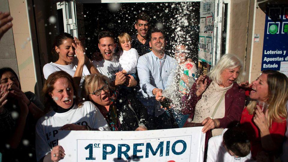 """Vor einer Bar in Spanien stehen Gewinner von """"El Gordo"""" mit einem Riesen-Los und verspritzen vor Freude Sekt"""