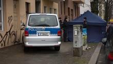 Ein Polizeiauto neben einem Zelt, in dem die Spurensicherung nach dem Fund einer Frauenleiche in Berlin arbeitet