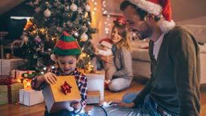 Eine Familie sitzt vorm Weihnachtsbaum und öffnet ihre Geschenke
