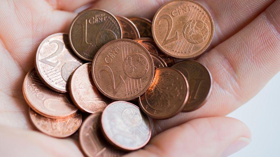 Ein- und Zwei-Cent-Münzen in einer Hand