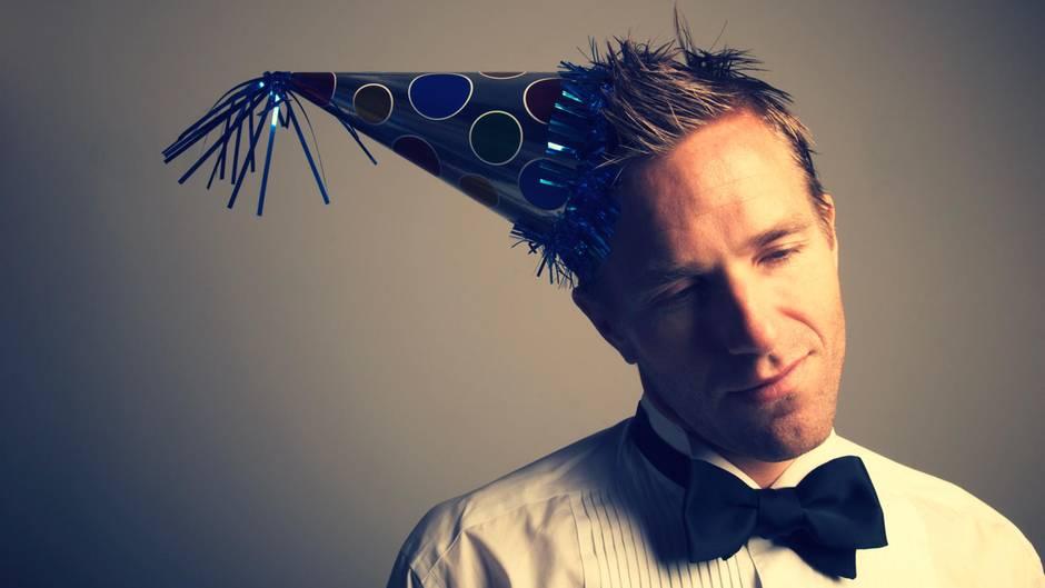 Ein einsamer Mann mit Partyhut. Feiert er Silvester allein?