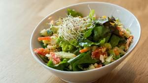 Eine Schüssel mit Salat steht auf einem Tisch