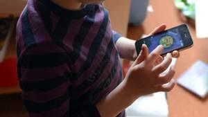 Ein Kind hält ein Smartphone in seinen Händen und spielt darauf