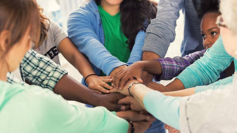 Menschen verschiedenen Alters und verschiedener Hautfarbe legen ihre Hände übereinander